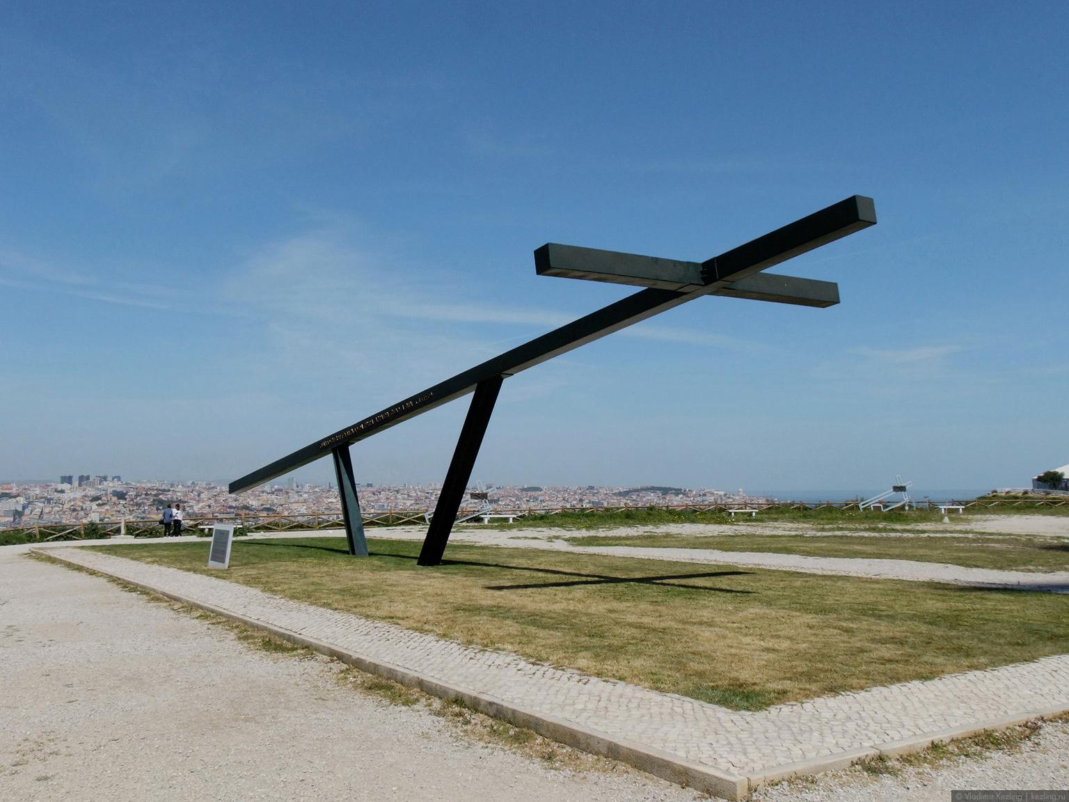 Крест перед статуей